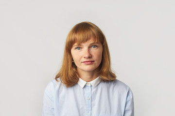 Headshot of young female model with ginger hair and freckles dressed in blue shirt looking at the camera. Isolated on white background