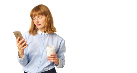 Portrait of young redheaded woman with freckles and bang talking on a phone looking at the screen smiling and holding a cup of coffee in her hands