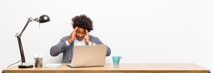 young black businessman looking stressed and frustrated, working under pressure with a headache and troubled with problems on a desk