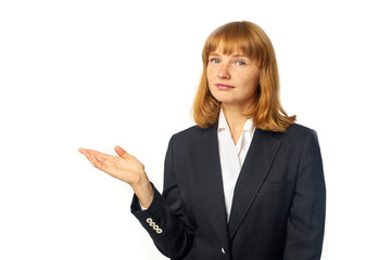 Image of young female office worker dressed in dark blazer and white shirt. Redheaded woman in business outfit showing with her hand to the copy space