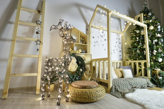 Beautiful children's playroom with wooden furniture, a house and a staircase, decorated for the New Year holiday with a Christmas tree, toys, gifts and a luminous deer made of garland