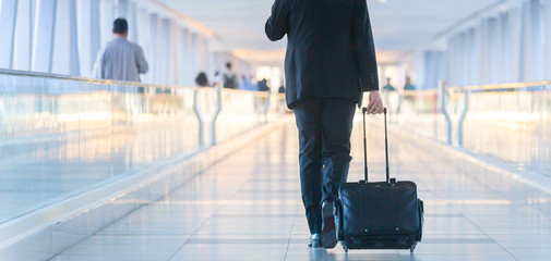 Rear view of unrecognizable formaly dressed businessman walking and wheeling a trolley suitcase at the lobby, talking on a mobile phone. Business travel concept. Fotobehang
