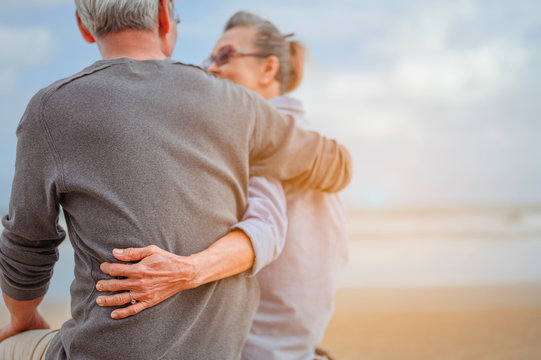 Retirement couple sitting by the sea, women embrace husbands and look at each other at the beach in the morning, life insurance plan at the retirement concept.