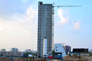 Mobile concrete batching plant at the construction site on the background of a tower crane and a multi-storey residential complex under construction - Image
