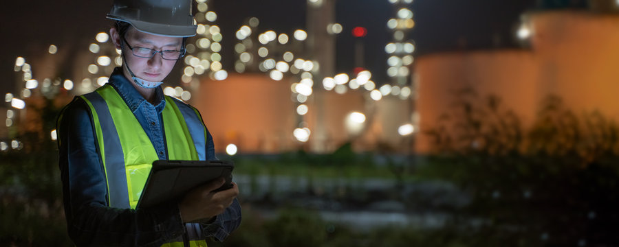 Engineer Petrochemical Asian man work late and hard with Smart tablet Inside the Refinery oil and gas,horizontal banner for website design,Industry,Fact