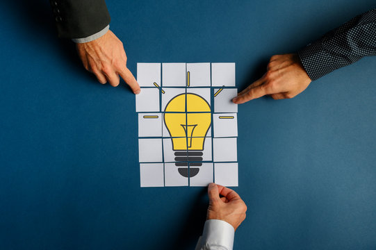 Hands of three businessmen assembling a lightbulb drawn on post it papers