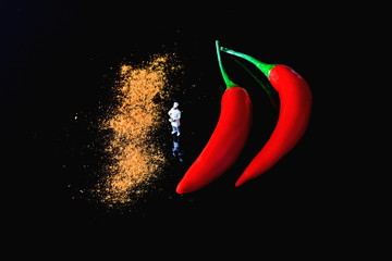 Canvas Prints Hot chili peppers red hot chili pepper on black background and miniature chef cooking