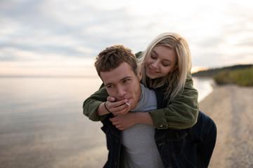 Smiling woman sharing cigarette to boyfriend near lake