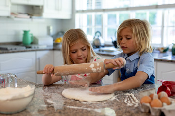Brother and sister making Christmas cookies at home