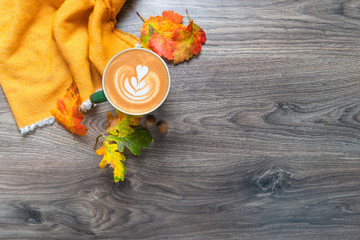 Fall leaves with a cup of coffee and a punch on a wooden board