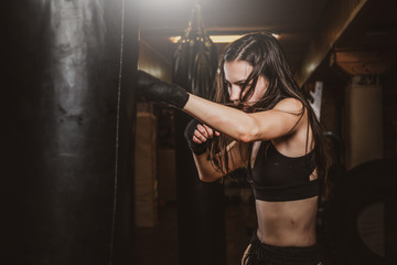Skinny focused woman has a boxing training with punching bag at dark gym.