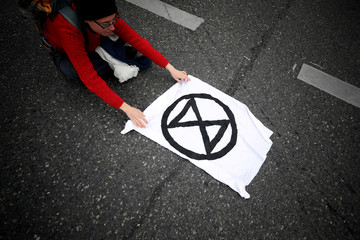 A climate change activist stretches a banner with the logo of the Extinction Rebellion as they block a road during a protest in Vienna
