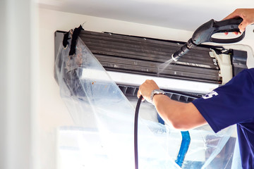 Obraz The technicians are cleaning the air conditioner by spraying water. Hand and water spray are cleaning the air conditioner on white background. - fototapety do salonu