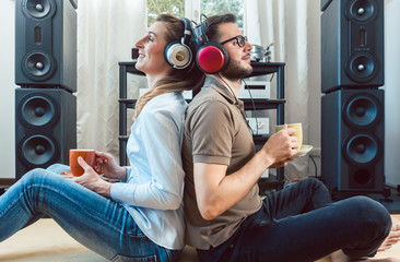 Couple with headphones enjoying music from the Hi-Fi stereo