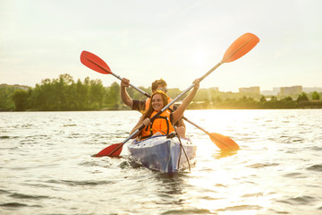 Happy young caucasian couple kayaking on river with sunset in the backgrounds. Having fun in...