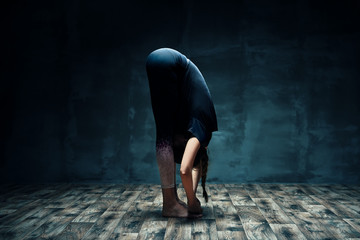 Young woman doing yoga standing forward bend pose in dark room
