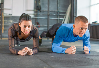 Fitness couple in gym makeing a plank exercise.