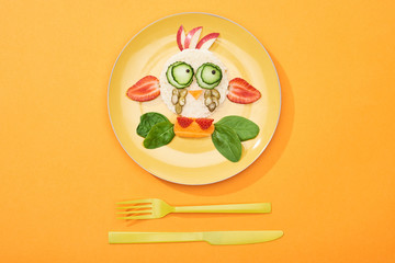 top view of plate with fancy cow made of food for childrens breakfast near cutlery on orange background