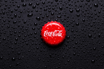 classic cap close-up of Coca-cola. Cap of cola on a black background with water drops.
