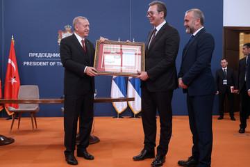 Turkish President Tayyip Erdogan and Serbian President Aleksandar Vucic exchange gifts after their meeting in Belgrade