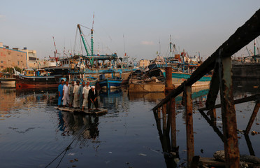 Fishermen sail on an improvised raft with anchored fishing boats in the background as they are crossing next to a submerged pedestal bridge at Fish Harbor in Karachi,