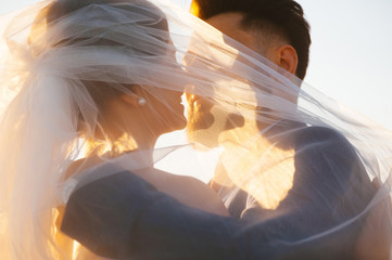 Bride and goom almost is kissing - close up image in the sunset light.
