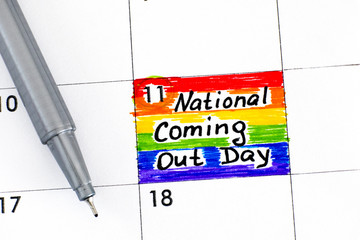 Reminder National Coming Out Day in calendar with pen.