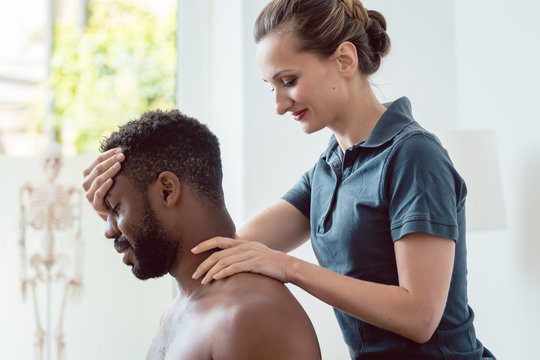 Woman physical therapist massaging young black man