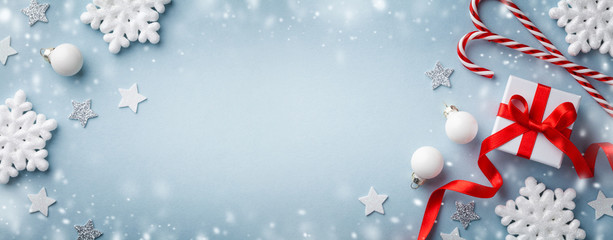 Christmas background with snow effect. Gift or present box, white snowflakes and holiday decoration top view. Happy New Year card.
