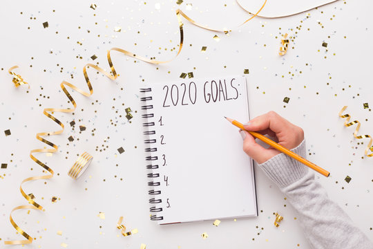 Woman writing down in notepad with 2020 goals
