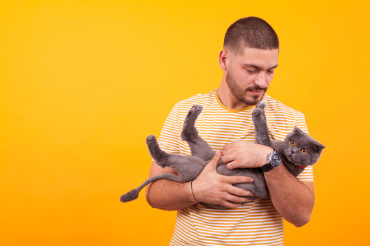 Handsome young man loving and holding his cat