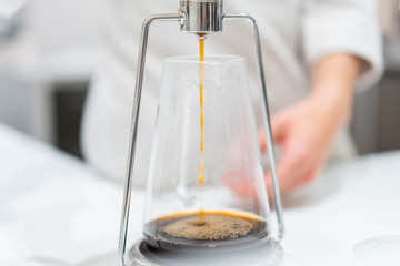 process of preparation black coffee in chemex pour over coffee maker in bright modern cafe. Alternative ways of brewing coffee.