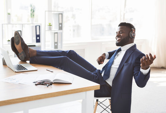 Young relaxed businessman having fun at office
