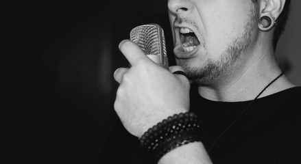Man screaming on the microphone. Singing heavy metal. Close-up on a man wearing black, holding a studio microphone.