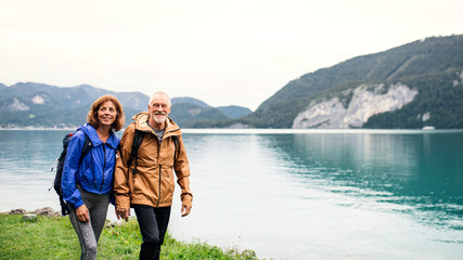 A senior pensioner couple hiking by lake in nature, holding hands.