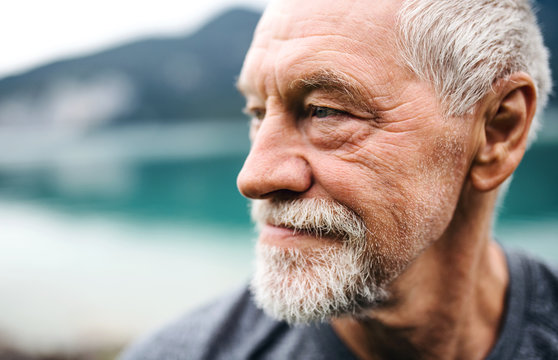 A close-up portrait of senior man pensioner standing outdoors in nature.