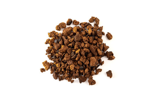 a pile of natural and wild chaga mushroom pieces on white background