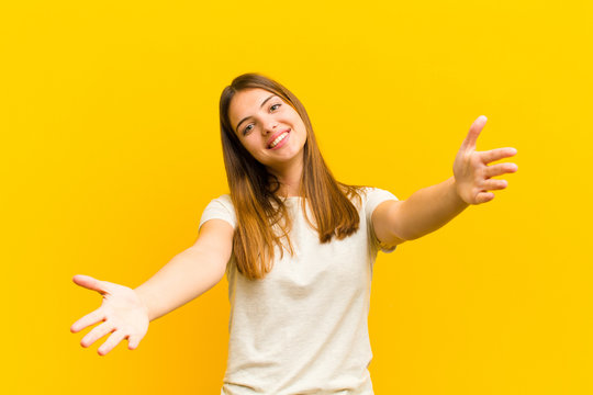 young pretty woman smiling cheerfully giving a warm, friendly, loving welcome hug, feeling happy and adorable against orange background