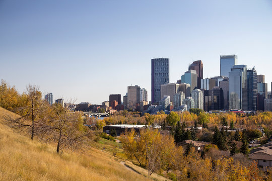 Autumn view of downtown Calgary, fall foliage, buildings, Centre street bridge and a hill
