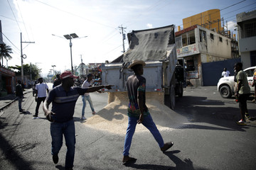 A protester gives directions as a truck unloads sand to set a barricade in a protest to demand the resignation of Haitian president Jovenel Moise, in the streets of Port-au-Prince