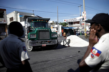 Haitian National Police (PNH) officers look on as a protester gives directions after a truck unloaded sand to set a barricade in a protest to demand the resignation of Haitian president Jovenel Moise, in the streets of Port-au-Prince