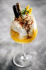 mango and passion fruit tropical ice cream sundae in glass
