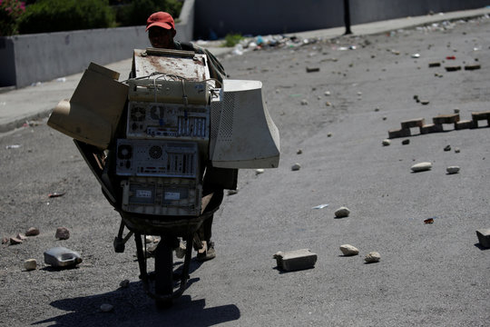 A man pushing a wheel barrow loaded with old screens and computers pass by a street blocked at Champs de Mars, in Port-au-Prince