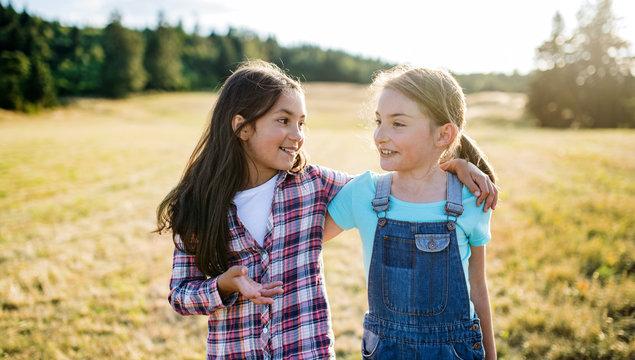 Two school children walking on field trip in nature, talking.