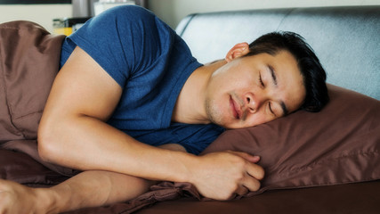 Asian young man sleeps on a brown bed.