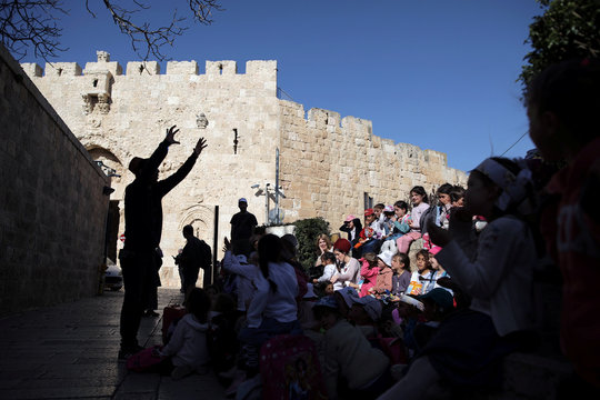 A man is silhouetted as he speaks to a group of children near Zion Gate in Jerusalem's Old City