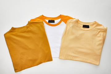 top view of beige, ochre and orange folded t-shirts on white background