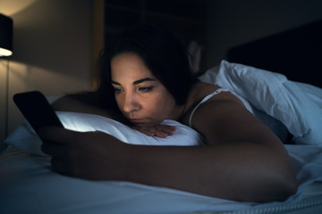 Young woman or girl using smartphone app social media while lying in bed at night