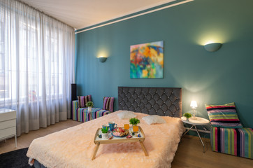 Modern interior of spacious studio apartment. Bedroom. King-size bed.
