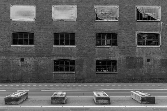 Public road with road blocks in the shape of giant Lego blocks to keep traffic separated with in the background on old factory building